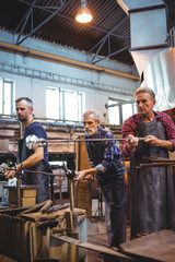 Team of glassblowers shaping a glass on the blowpipe