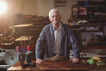 Portrait of senior cobbler standing in workshop