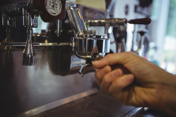 Waitress holding portafilter filled with ground coffee