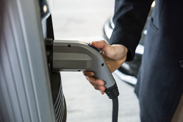 Man charging car at electric vehicle charging station