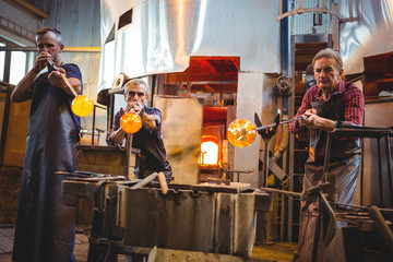 Team of glassblowers shaping a glass on the blowpip