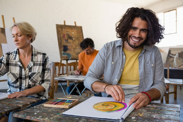 Portrait of smiling man practicing drawing while sitting with friends