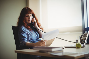 Pregnant businesswoman talking on telephone while working
