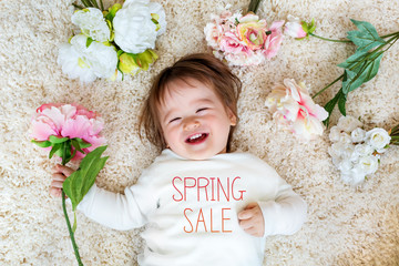 Spring Sale message with happy toddler boy with spring flowers