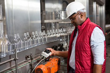 Male employee operating machine in juice factory