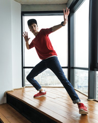 Teenager in red sweater and baseball cap, jeans and sneakers dances by window in dance studio. Modern dance. Hip-hop movement. Dynamics of dance