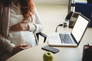 Mid-section of pregnant businesswoman holding her belly