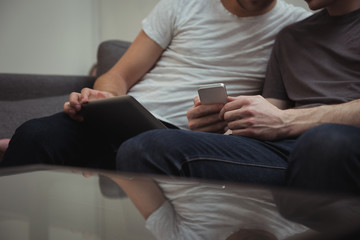 Gay couple sitting on sofa and looking at digital tablet