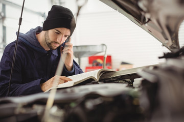 Mechanic reading instruction manual while talking on a mobile phone