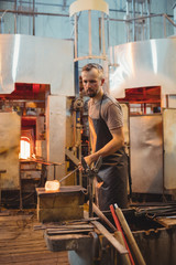 Glassblower shaping a molten glass on marver table