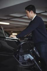 Man using laptop while charging electric car