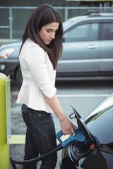 Beautiful woman charging electric car