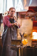 Glassblower blowing glass through blowpipe in workshop