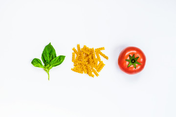 Top view of pasta ingredients over white background - raw fusilli, fresh basil and ripe tomatoe. Italian food concept.