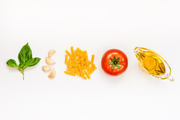 Top view of pasta ingredients over white background - raw fusilli, fresh basil, garlic cloves, olive oil and ripe tomatoe. Italian food minimal concept.