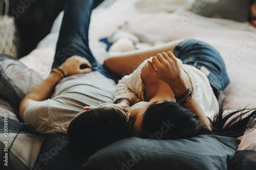 attractive romantic couple laying on bed hugging and kissing in a