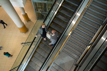 Businesspeople interacting with each other while moving down on escalator