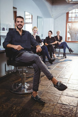 Smiling hairdressers sitting on chair in salon