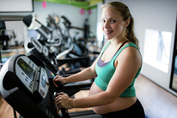 Pregnant woman exercising on treadmill
