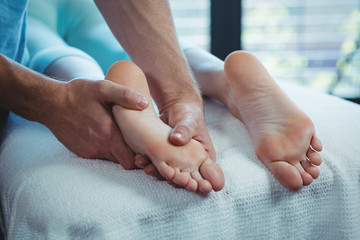 Male physiotherapist giving foot massage to female patient