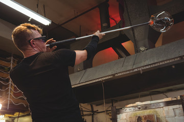 Glassblower shaping a piece of glass on the blowpipe