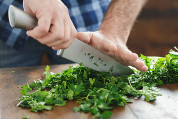 Foto auf Acrylglas Kochen Close up male hands chopping fresh parsley