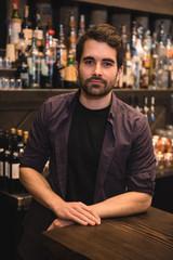 Confident bartender standing at bar counter