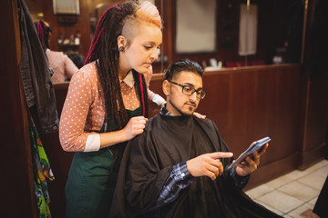 Client showing digital tablet to female barber