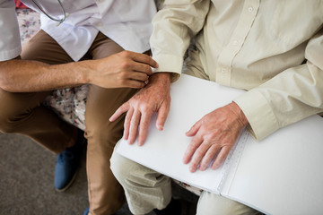 Blind senior man using braille to read