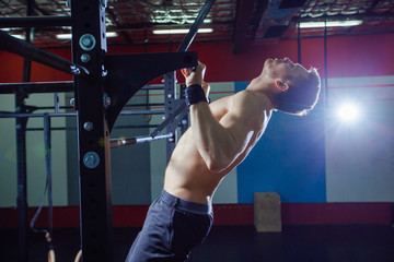Athlete muscular fitness male model pulling up on horizontal bar in a gym. Cross fit style