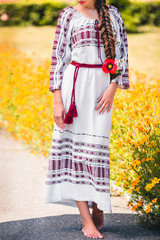 girl is dressed in a long embroidered dress with patterns