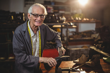 Portrait of shoemaker working in workshop