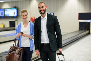 Couple standing with luggage at waiting area in airport