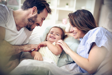 Parents playing with their daughter.