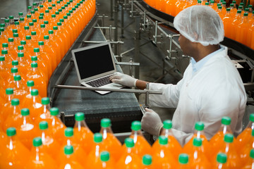 Male worker using laptop amidst production line in juice factory