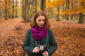 Young woman with camera standing outdoors