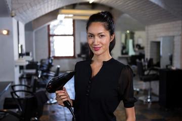 Smiling female hairdresser holding brush in hair salon