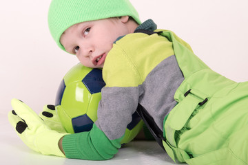 A happy and charming blond blond child in a new sports suit and bright green shoes is teaching at home. Green Soccer ball. Physical training for kindergartens and preschool children. White background