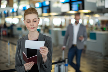 Smiling businesswoman checking her boarding pass