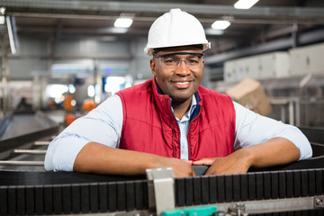 Smiling male employee standing by conveyor belt in factory