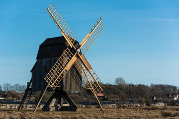 Evening sunlight hits the old wooden windmill at Nasby village on Oland, Sweden.