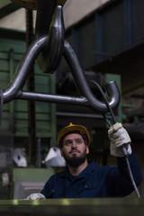 Technician adjusting metal equipment in hook