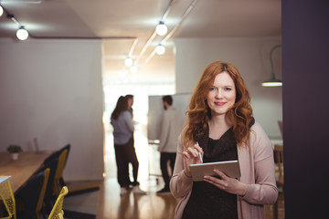 Portrait of smiling young woman with digital tablet standing indoors