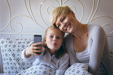 Mother and daughter taking selfie while sitting on bed