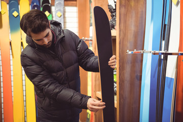 Man selecting ski in a shop