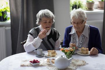 Senior friends having breakfast at home