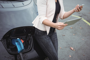Mid section of woman using mobile pone while charging electric car