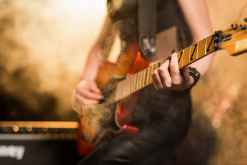 Female guitar player in stage lights