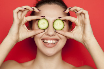 Happy young woman posing with slices of cucumber on her face on red background