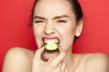Frowning young woman biting slice of cucumber on red background